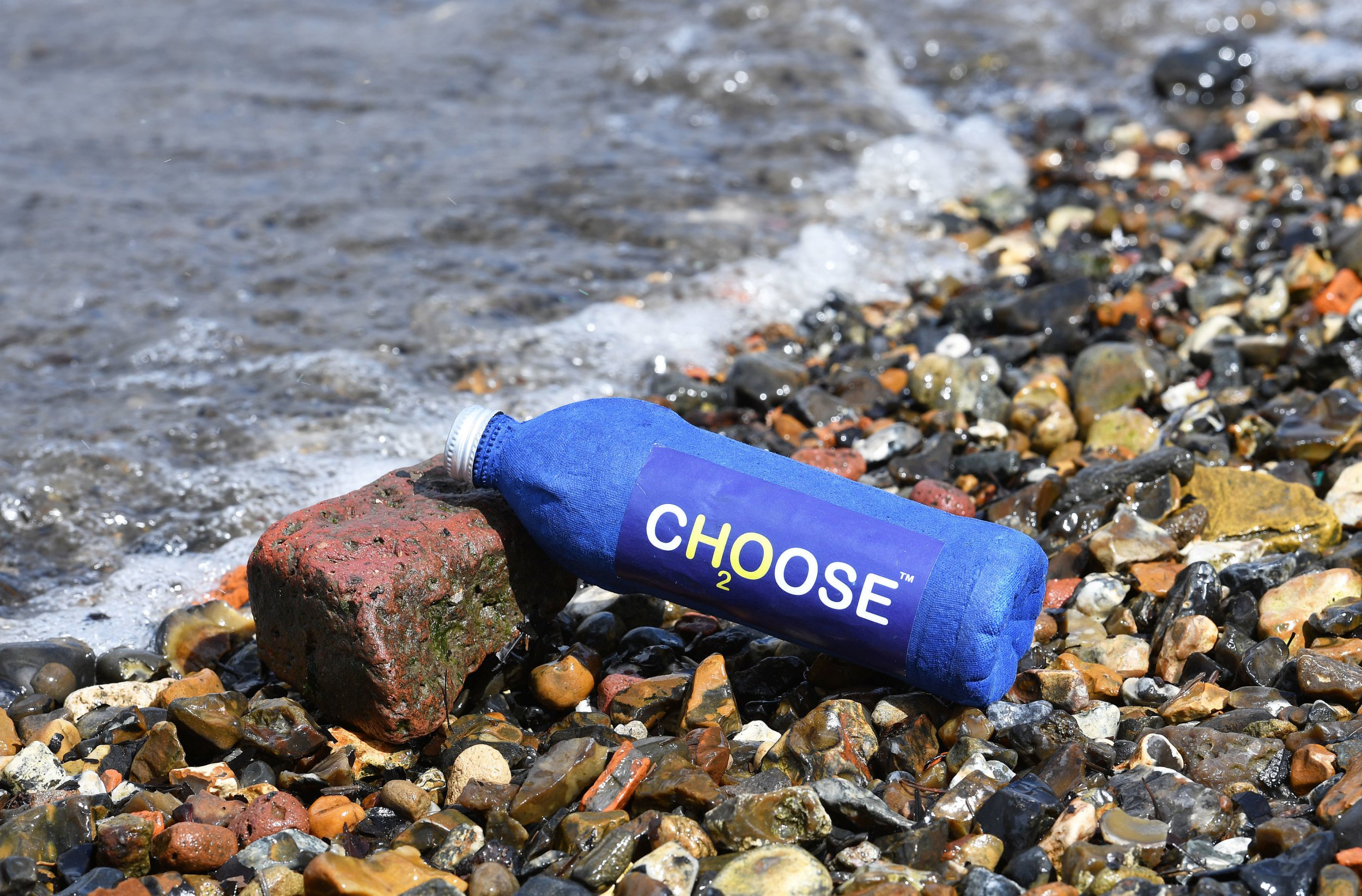 A Choose Water bottle on the shore of the ocean