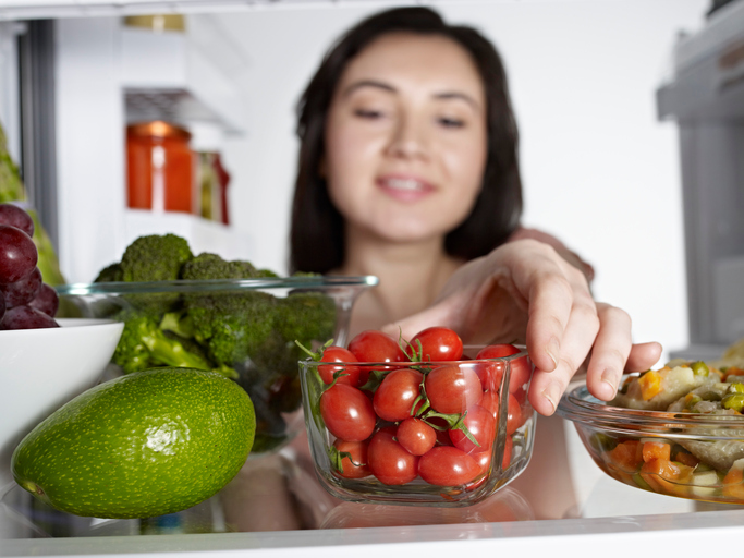Woman taking cherry tomato from fridge.