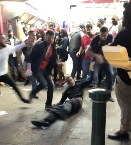 Screen-grab from a video showing a man on the floor during a mass drunken brawl on Broad Street, Birmingham, UK, in the early hours of Sunday 3rd June, 2018. The shocking fight, captured on camera by a passer-by, involved at least 12 people and can only be described as carnage. A SHOCKING clip has emerged of a mass brawl which ends in ELEVEN men and one woman kicking and punching each other outside a takeaway. During the astonishing altercation ? which took place at around 4am on Sunday 3rd June in Birmingham City Centre ? bewildered onlookers watch as the gang of men throw blows at each other and fall injured on the street. The man ? who recorded the footage and asked not to be named ?claimed that the fight was so chaotic that eight police officers who were present in the area were too afraid to intervene until the brawl was over. The footage was filmed by a passer-by after he saw the violent fight unfolding outside Pit Stop Takeaway on Broad Street, Birmingham in the early hours of Sunday morning. The video begins showing the eleven men and one woman in the midst of a mass brawl as daylight begins to break. ... SEE COPY AND VID ... PIC BY NEWS DOG MEDIA ... 0121 517 0019