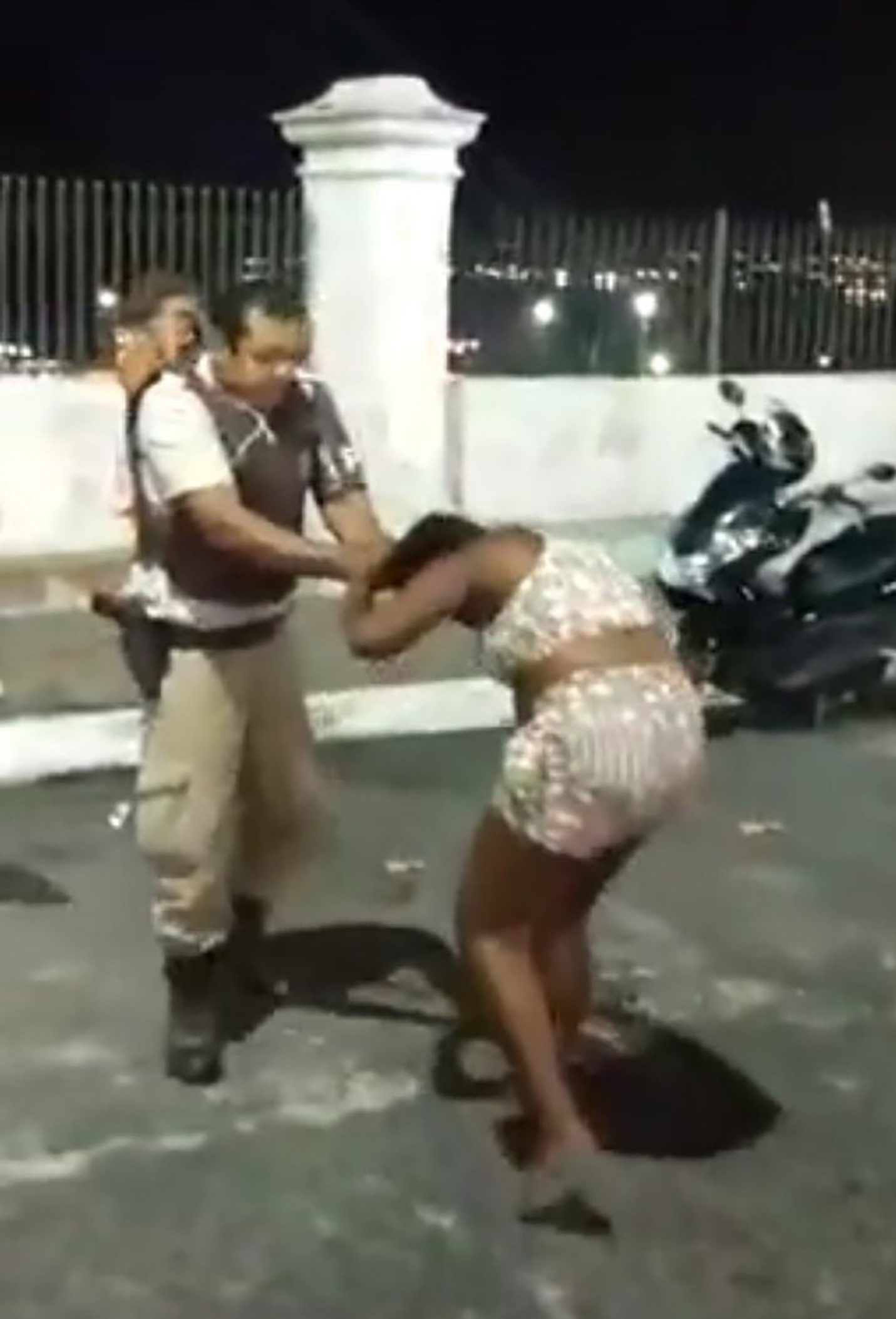 """Pic shows: The soldier drags the woman by the hair and punches her This is the shocking moment a cop brutally drags a pregnant woman by her hair and repeatedly hits her in the face in front of a crowd of onlookers. The startling scenes were filmed in the Santo Antonio Alem do Carmo area of the city of Salvador, in the Brazilian state of Bahia. In the video, the woman can be heard shouting at the cops who are arresting a man at the back of their patrol car. One of the cops then walks up to the crowd of onlookers and grabs the woman by her hair and begins slamming his fist into her face. He then then drags the woman away from the crowd by her hair as an onlooker can be heard shouting """"Calm down man! She is pregnant!"""". The suspect who was being arrested can be seen struggling with officers in the background as the crowd tries to drag the woman away from the aggressive cop. The officer then lands another punch on the pregnant woman???s face before onlookers manage to drag her to safety. The woman, who does not wish to be named, confirmed she is three months pregnant. She told reporters: """"The officer who hit my face was not with the same patrol as those who beat the boy (getting arrested). We started shouting because there were a lot of people, a lot of families, we shouted that they were cowards and they were going to kill the boy. """"He did not say anything to me, he did not address me, he came and hit me and people were asking him to let me go. He hit me really hard in the face, people were shouting that I was pregnant and he continued attacking me."""" She said that nobody knew the boy who was being arrested. The Military Police confirmed they were investigating the video and the behaviour of the officers during the arrest. A statement read: """"The images are being analysed by the Commander and the officers, who clearly overstepped the mark, have been removed from operational activities."""" The officer who hit the woman has been suspended and is seeing a psychol"""