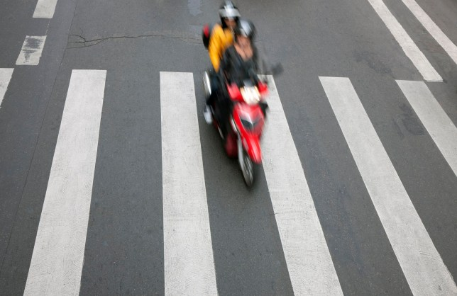couple riding moped down city street, view from above, blurred motion