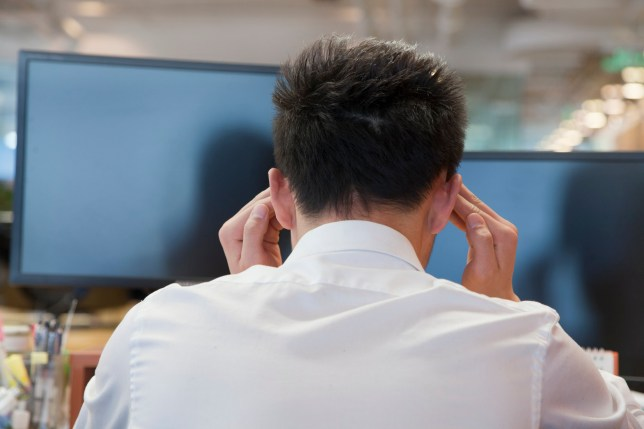 Chinese businessman rubbing his temples at desk