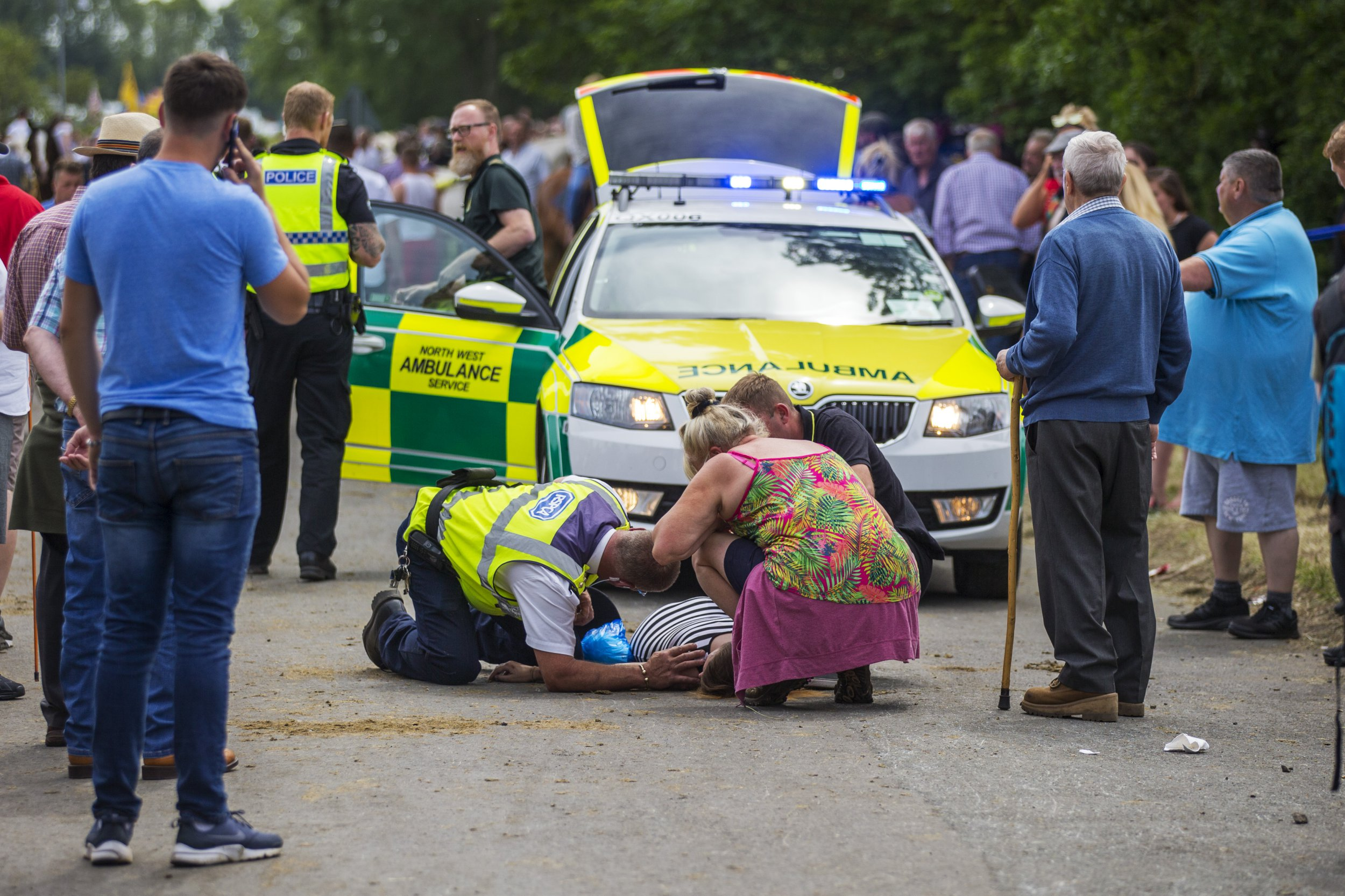 ? London News Pictures Ltd. 08/06/2018 Appleby UK. A young woman lying unconscious with a head injury after being hit by travellers racing a horse & cart on a road in Appleby. The Appleby Horse fair is taking place this weekend & is billed as the biggest Traveller & Gypsy fair in Europe attracting over 10,000 travellers & 30,000 visitors to the town of Appleby in Cumbria. Photo Credit: Andrew McCaren/LNP