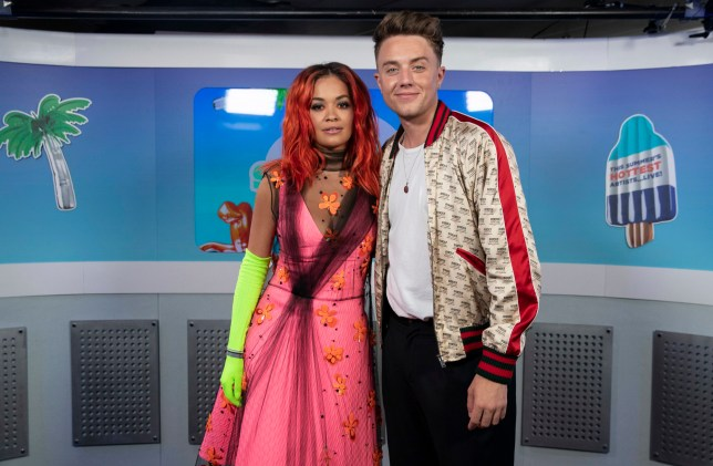Rita Ora and Roman Kemp in the on air studio during Capital's Summertime Ball with Vodafone at Wembley Stadium, London. PRESS ASSOCIATION Photo. This summer's hottest artists performed live for 80,000 Capital listeners at Wembley Stadium at the UK's biggest summer party. Performers included Camila Cabello, Shawn Mendes, Rita Ora, Charlie Puth, Jess Glyne, Craig David, Anne-Marie, Rudimental, Sean Paul, Clean Bandit, James Arthur, Sigala, Years & Years, Jax Jones, Raye, Jonas Blue, Mabel, Stefflon Don, Yungen and G-Eazy. Picture date: Saturday June 9, 2018. Photo credit should read: Lauren Hurley/PA Wire