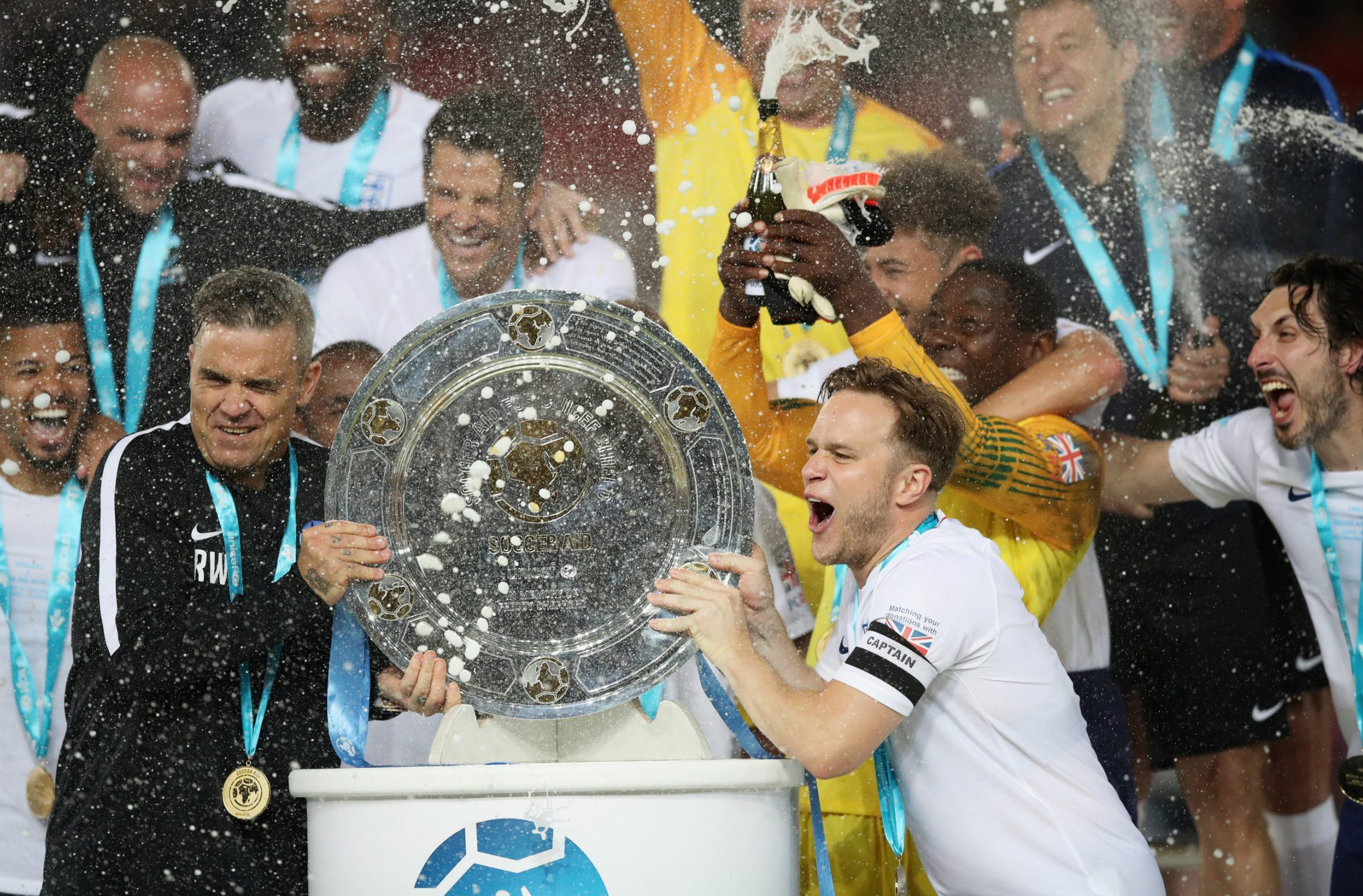 MANCHESTER, ENGLAND - JUNE 10: Olly Murs of England lifts the trophy in victory with Robbie Williams of England and team mates after the Soccer Aid for UNICEF 2018 match between Englannd and the Rest of the World at Old Trafford on June 10, 2018 in Manchester, England. (Photo by Lynne Cameron/Getty Images)