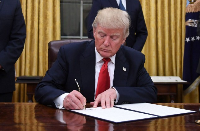 US President Donald Trump signs an executive order as Vice President Mike Pence looks on at the White House in Washington, DC on January 20, 2017. / AFP / JIM WATSON (Photo credit should read JIM WATSON/AFP/Getty Images)
