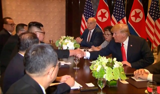 In this image made from video provided by Host Broadcaster Mediacorp Pte Ltd,, U.S. President Donald Trump and North Korean leader Kim Jong Un shake hands over a table during their meeting at Capella Hotel in Singapore, Tuesday, June 12, 2018. (Host Broadcaster Mediacorp Pte Ltd via AP)