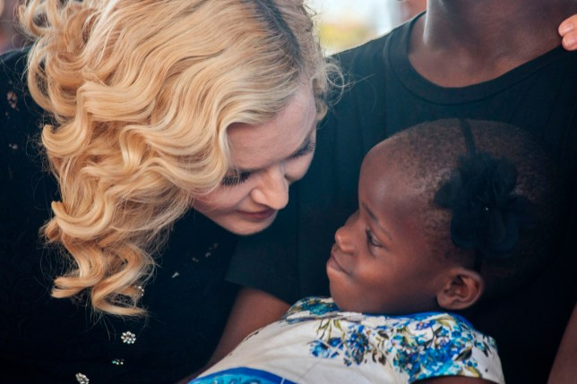 US pop star Madonna (L) speaks to one of her two newly adopted daughters at the opening ceremony of the Mercy James Children's Hospital at Queen Elizabeth Central Hospital in Blantyre, Malawi, on July 11, 2017. Madonna on July 11 took her four adopted Malawian children back to their home country for the opening of a paediatric hospital wing that her charity has built. / AFP PHOTO / AMOS GUMULIRA (Photo credit should read AMOS GUMULIRA/AFP/Getty Images)