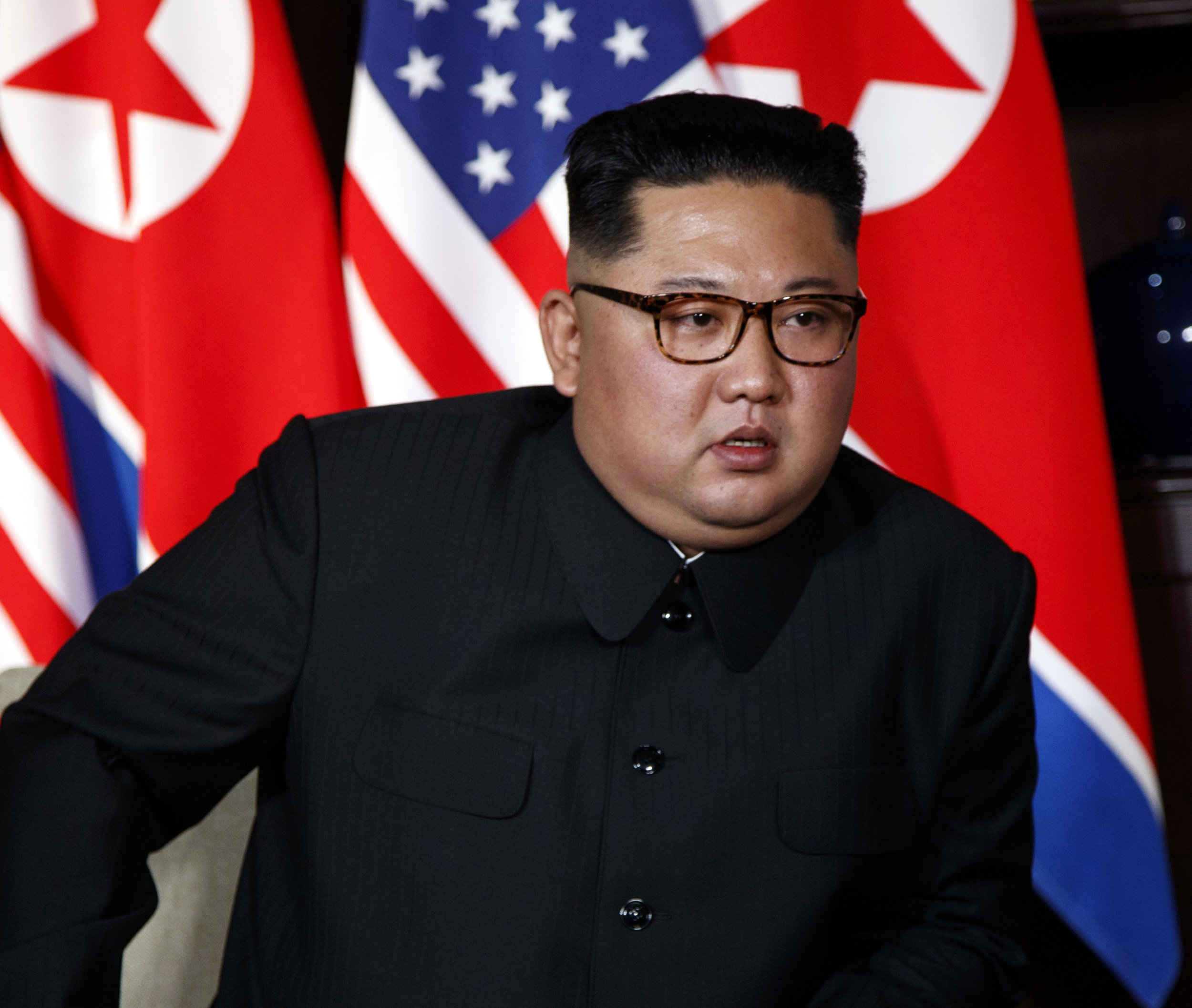 FILE - In this June 12, 2018, file photo, North Korean leader Kim Jong Un listens to U.S. President Donald Trump during a meeting on Sentosa Island in Singapore. Chinese state media say North Korean leader Kim will make a two-day state visit starting Tuesday, June 19. Kim's trip follows his groundbreaking summit with President Donald Trump in Singapore last week that resulted in a surprise announcement of a U.S. suspension of military drills with its South Korean ally.(AP Photo/Evan Vucci, File)