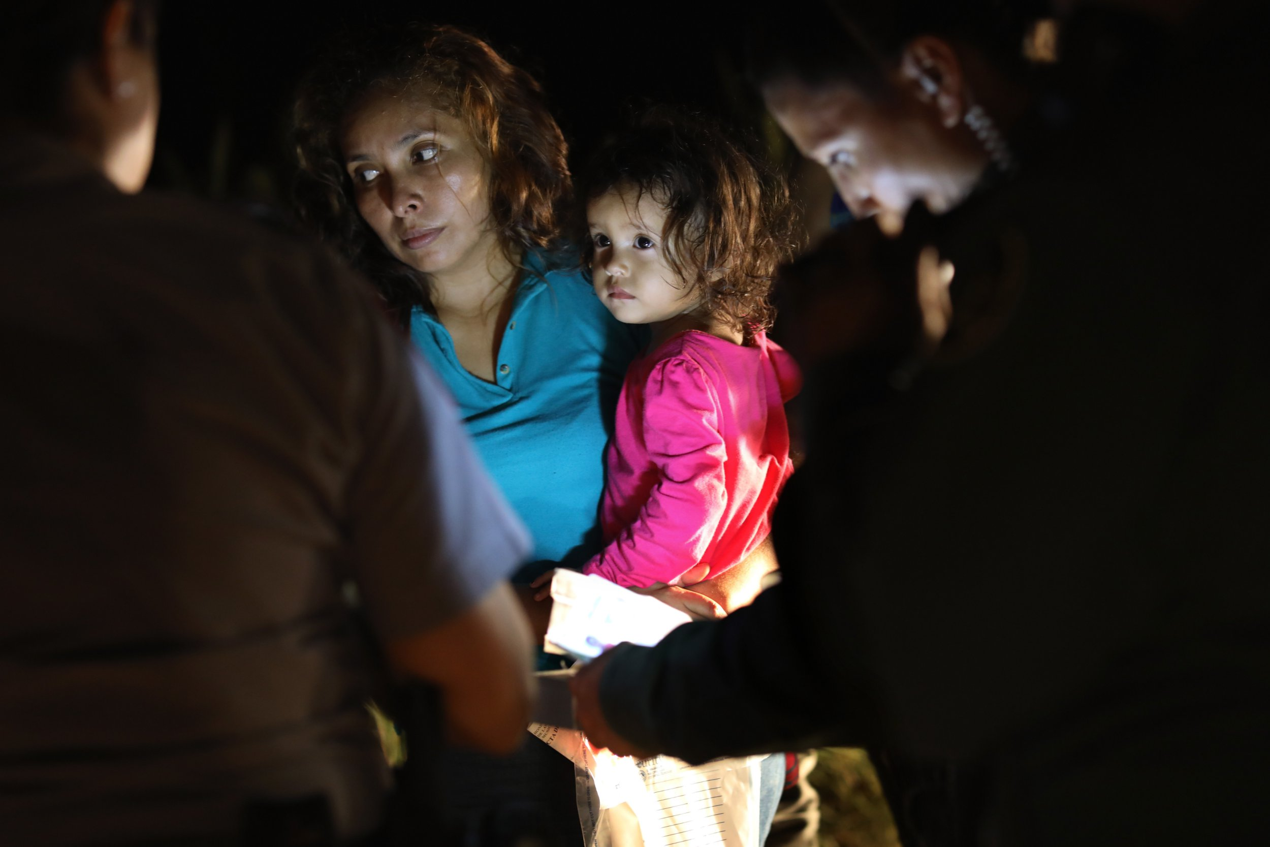 """MCALLEN, TX - JUNE 12: A Honduran mother holds her two-year-old as U.S. Border Patrol as agents review their papers near the U.S.-Mexico border on June 12, 2018 in McAllen, Texas. The asylum seekers had rafted across the Rio Grande from Mexico and were detained by U.S. Border Patrol agents before being sent to a processing center for possible separation. Customs and Border Protection (CBP) is executing the Trump administration's """"zero tolerance"""" policy towards undocumented immigrants. U.S. Attorney General Jeff Sessions also said that domestic and gang violence in immigrants' country of origin would no longer qualify them for political asylum status. (Photo by John Moore/Getty Images)"""
