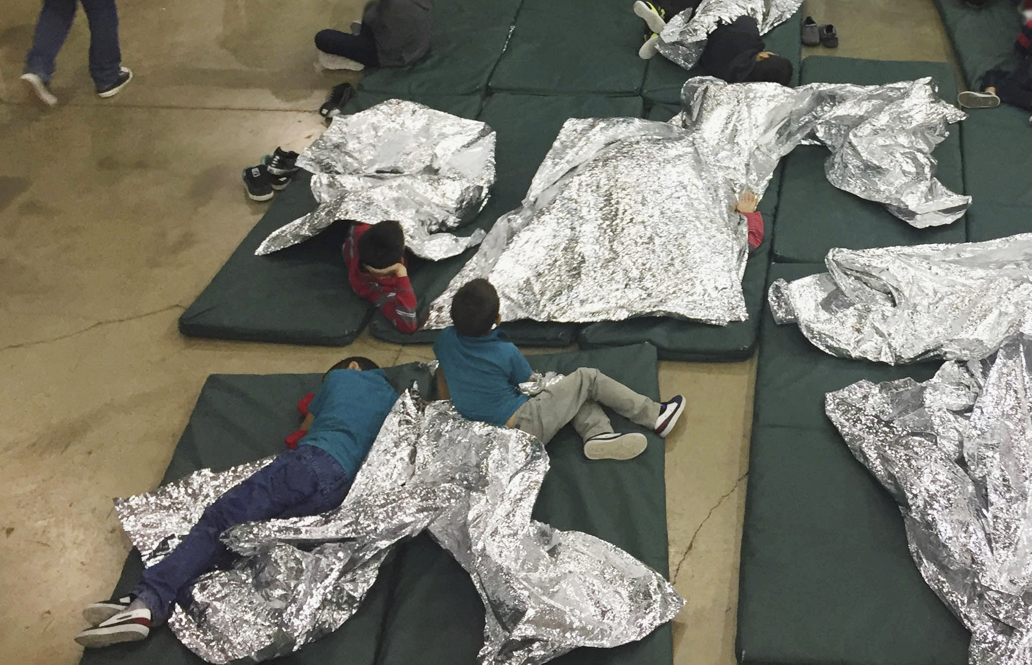 FILE - In this Sunday, June 17, 2018, file photo provided by U.S. Customs and Border Protection, people who've been taken into custody related to cases of illegal entry into the United States, rest in one of the cages at a facility in McAllen, Texas. Child welfare agencies across America make wrenching decisions every day to separate children from their parents. But those agencies have ways of minimizing the trauma that aren't being employed by the Trump administration at the Mexican border. (U.S. Customs and Border Protection's Rio Grande Valley Sector via AP, File)