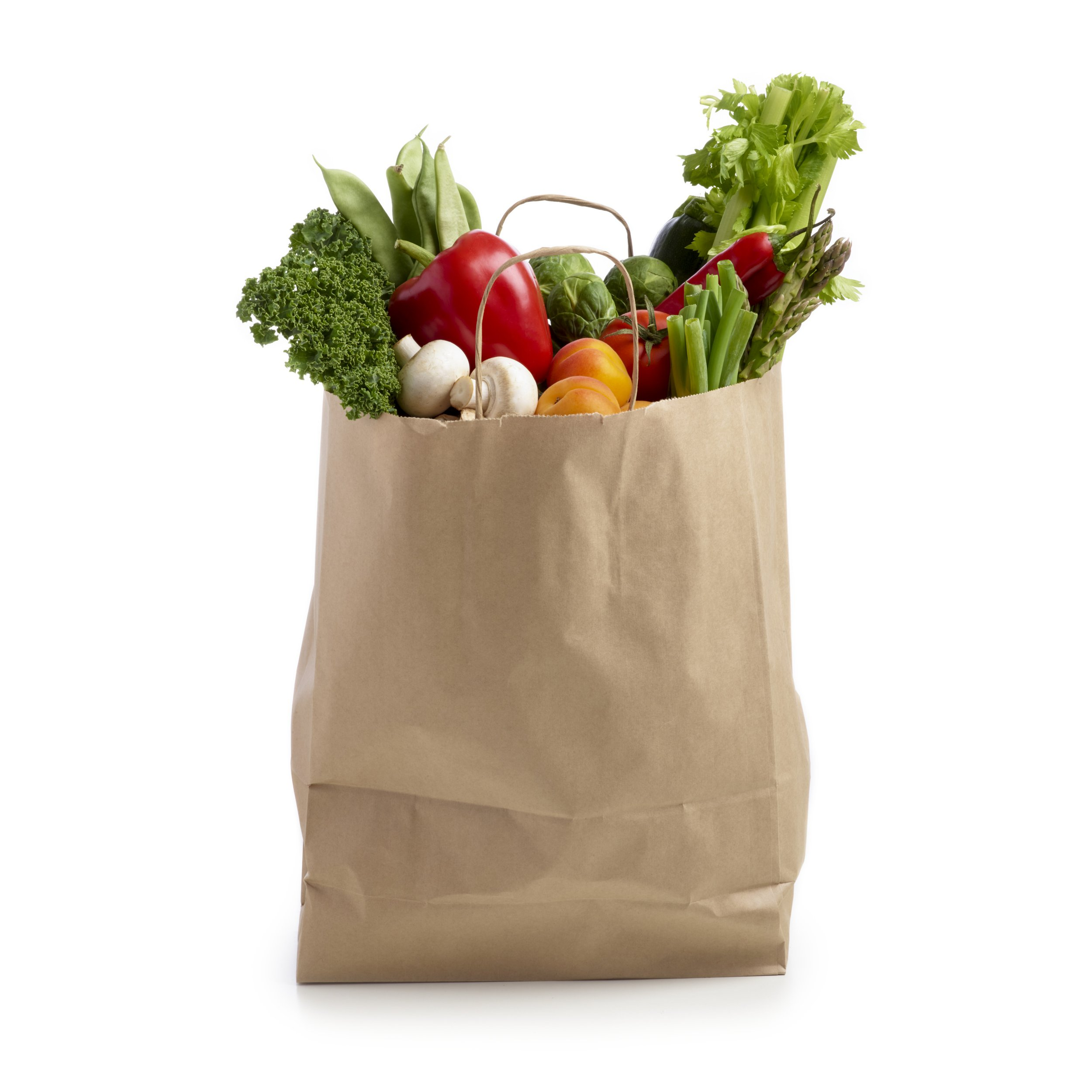 Shopping bag full of fresh produce against a white background.