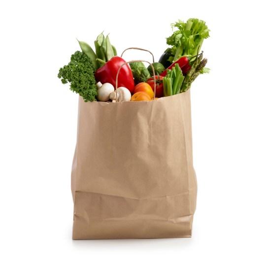 Shopping bag full of fresh produce against a white background.