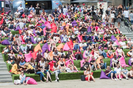 Alamy Live News. P5J9YX London UK. 27th June 2018. Large crowds of people enjoy the summer sunshine during lunchtime in Granary Square London on special cushions as they watch a Summer of Love entertainment on another hot day in the capital with temperatures reaching the high twnties Credit: amer ghazzal/Alamy Live News This is an Alamy Live News image and may not be part of your current Alamy deal . If you are unsure, please contact our sales team to check.