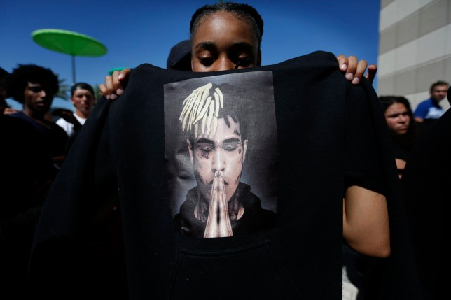 Anneyah Lawson, 14, of St. Petersburg, Fla., holds up a sweatshirt with an image of slain rapper XXXTentacion, before his memorial on Wednesday, June 27, 2018, in Sunrise, Fla. The rapper was gunned down in a luxury sports car last week. (AP Photo/Brynn Anderson)