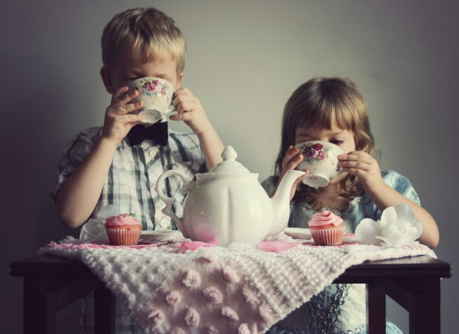 Little boy and little girl drinking tea in fancy clothes with pretty pink cupcakes and decor.