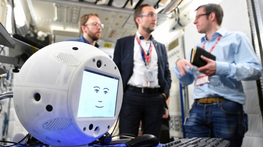 "This Jan. 30, 2018 photo provided by the German Aerospace Center shows the ""Cimon"" (Crew Interactive MObile companioN) robot during a communications test at the ESA European Astronaut Center in Cologne-Porz, Germany. The round, artificial intelligence robot is part of SpaceX's latest delivery to the International Space Station. Liftoff is set for early Friday, June 29, 2018, from Cape Canaveral, Fla. In the background from left are project leaders Christian Karrasch, Till Eisenberg and Christoph Kossl. (T. Bourry/ESA/DLR via AP)"
