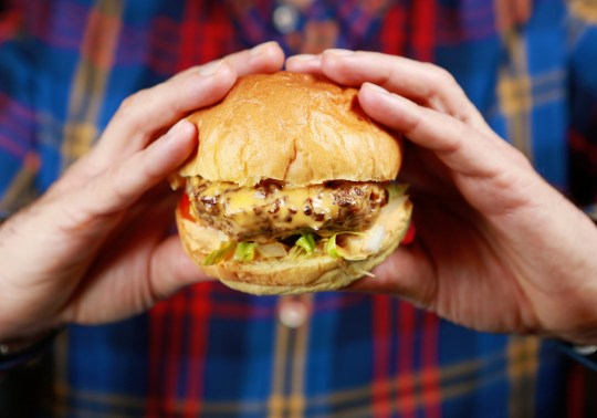 A delicious looking meaty cheese burger in the hands of a lucky diner.
