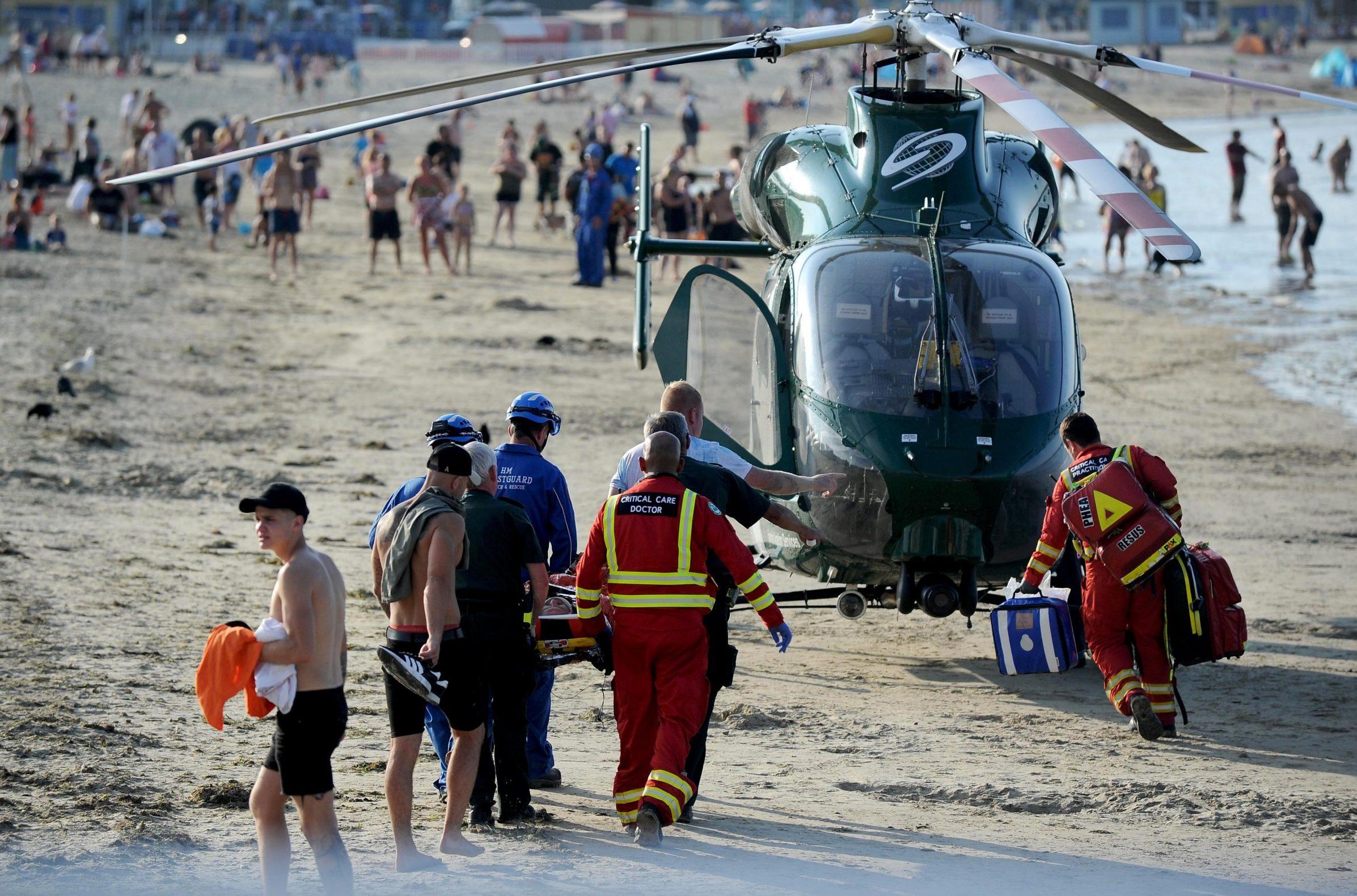 Mandatory Credit: Photo by Finbarr Webster/REX/Shutterstock (9731716e) An injured man is stretchered onto an air ambulance after an incident on Weymouth beach Injured man airlifted from Weymouth beach, Dorset - 30 Jun 2018