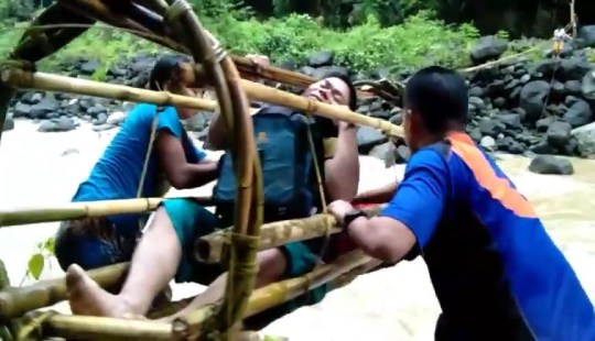 VIDEO STILLS -- ??????These kids make a terrifying trip to school every morning - suspended in a bamboo basket while pulling themselves across a raging river. The youngsters can normally wade through the shallow water but during the rainy season from June until October it turns into a raging torrent of rapids in Davao Oriental, the Philippines. Butay Integrated School is the only establishment in the area and their village is on the wrong side of the river - meaning they have to cross twice a day. Rather than get wet, the innovative teenagers fastened a huge length of bamboo between two trees and built a bamboo cage. They then climb inside with their backpacks and haul themselves across. Once they reach the other side, others waiting can pull the cage back with a second bamboo line which is fastened to it. Footage taken earlier this week captures their perilous school run. Local teenager Noel Gayoso said: ''When it's raining and the river's flooded this is the only way that we can cross. It's a little bit scary, but it's the best passage for us to reach school.'' ENDS