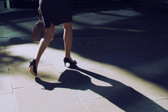 Elegant business woman on high heels is walking along street.