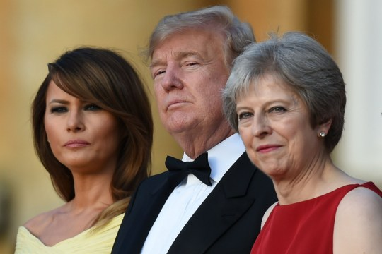 (L-R) US First Lady Melania Trump, US President Donald Trump and Britain's Prime Minister Theresa May stand on steps in the Great Court as the bands of the Scots, Irish and Welsh Guards perform a ceremonial welcome as they arrive for a black-tie dinner with business leaders at Blenheim Palace, west of London, on July 12, 2018, on the first day of President Trump's visit to the UK. The four-day trip, which will include talks with Prime Minister Theresa May, tea with Queen Elizabeth II and a private weekend in Scotland, is set to be greeted by a leftist-organised mass protest in London on Friday. / AFP PHOTO / POOL / Geoff PUGHGEOFF PUGH/AFP/Getty Images