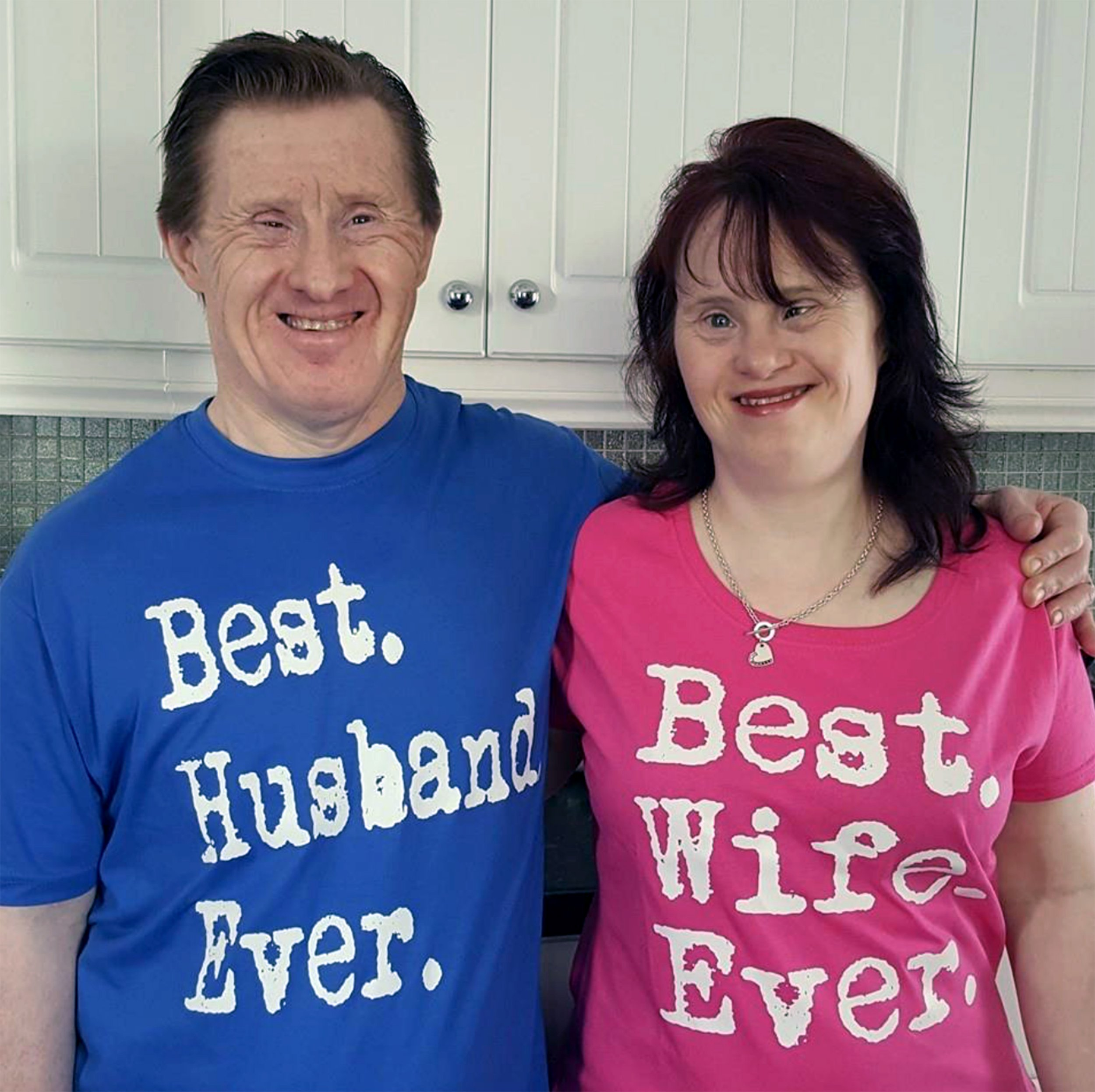 PIC FROM Caters News - (PICTURED: Maryanne and Tommy wearing their best husband/ wife tops) - A Downs Syndrome couple have proved doubters wrong after 23 years of wedded bliss and a huge Facebook following of people inspired by their heartwarming story. Maryanne and Tommy Pilling were thought to be the first Downs couple to tie the knot in 1995 but were hit by a wave of criticism. The pair had dated for around 18 months before Tommy popped the question and the couple went on to tie the knot at St Marys Church in Shoeburyness,Essex, in July 1995.SEE CATERS COPY