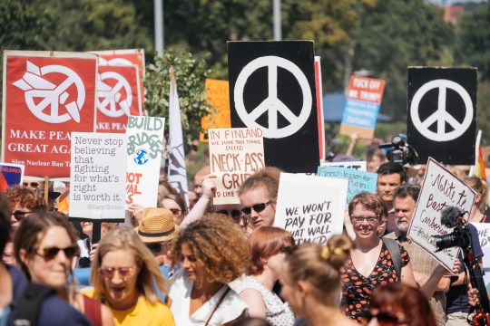 """People hold placards and banners during the so-called """"Helsinki Calling"""" march towards the Senate Square to defend the human rights, freedom of speech and democracy on July 15, 2018, ahead of the arrival of US President for a summit with his Russian counterpart in the Finnish capital Helsinki. / AFP PHOTO / Alessandro RAMPAZZOALESSANDRO RAMPAZZO/AFP/Getty Images"""