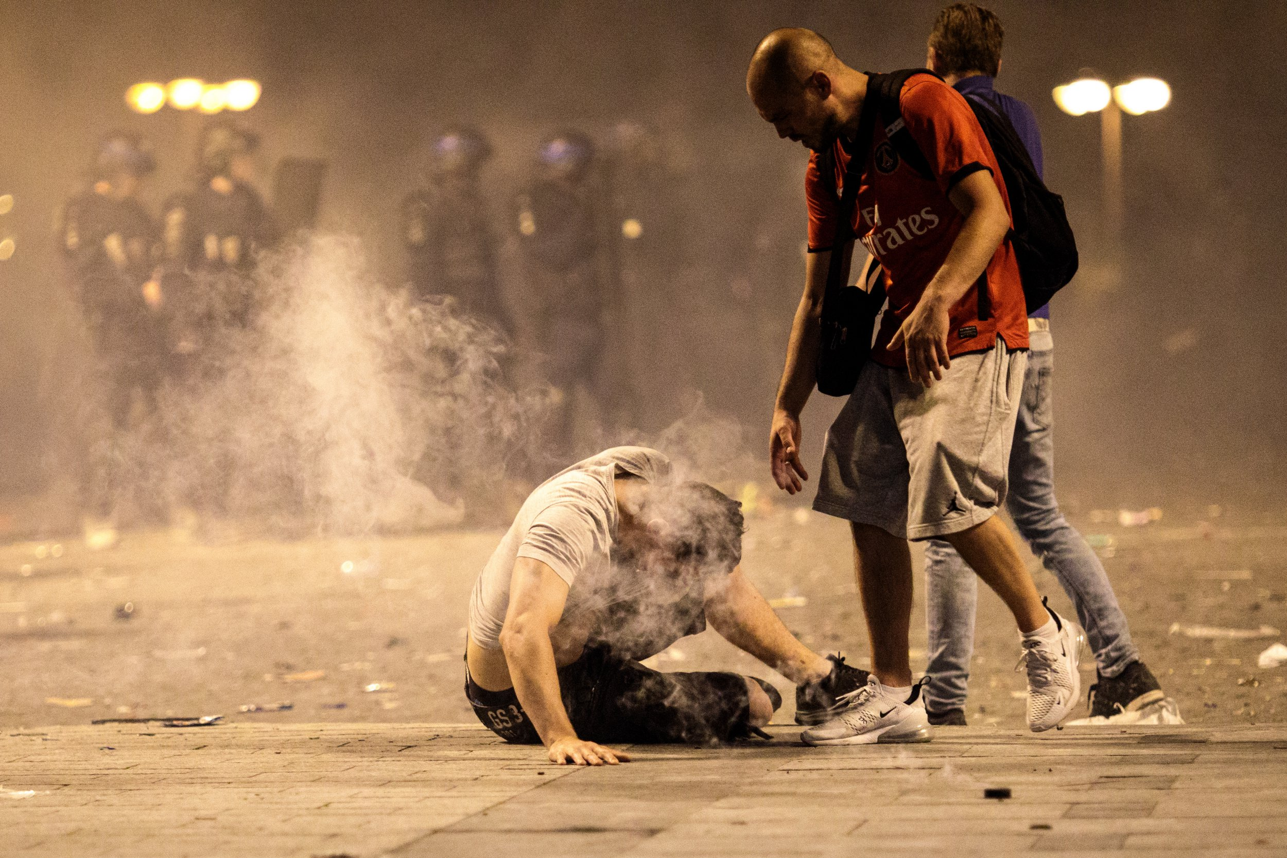 PARIS, FRANCE - JULY 15: A man falls to the floor after inhaling tear gas as French football fans clash with police following celebrations around the Arc de Triomph after France's victory against Croatia in the World Cup Final on July 15, 2018 in Paris, France. France beat Croatia 4-2 in the World Cup Final played at Moscow's Luzhniki Stadium today. (Photo by Jack Taylor/Getty Images)