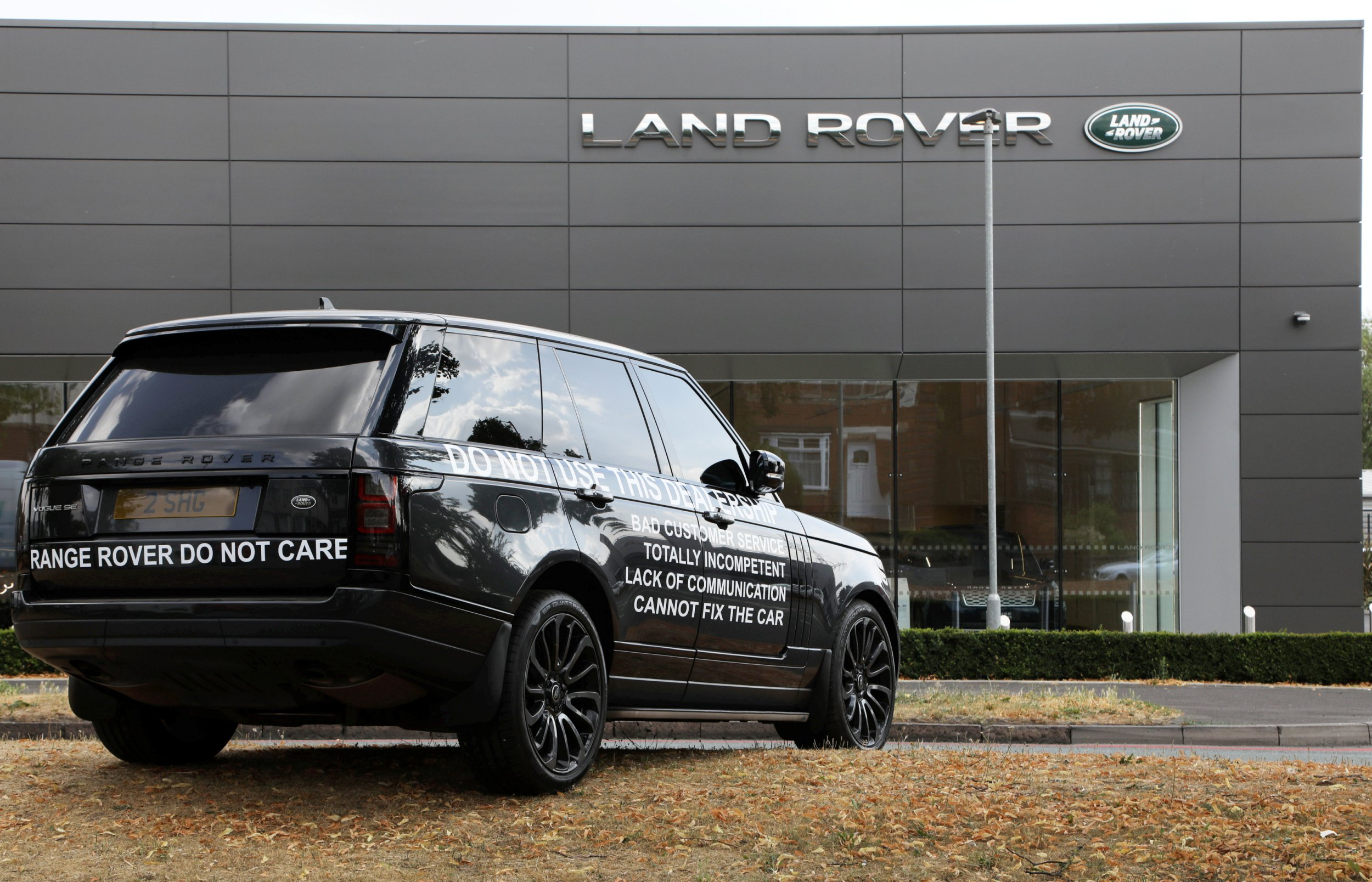 """A motorist has plastered their ?63,000 Range Rover Vogue with slogans and left it outside a Birmingham dealership in an apparent dispute. See NTI story NTIROVER. The Lancaster Land Rover customer parked the black 2016 vehicle on the central reservation, facing towards the Tyburn Road showroom in Erdington, Birmingham. The driver staged the one-car protest in an apparent bid to put off future customers. Stickers attached to both sides of the car read: """"Range Rover do not care. Do not use this dealership. Bad customer service, totally incompetent, lack of communication, cannot fix the car."""" The issues leading to the car being dumped were unclear. The dealership confirmed it was aware of the vehicle and staff were due to meet with the customer to 'agree a way forward'."""
