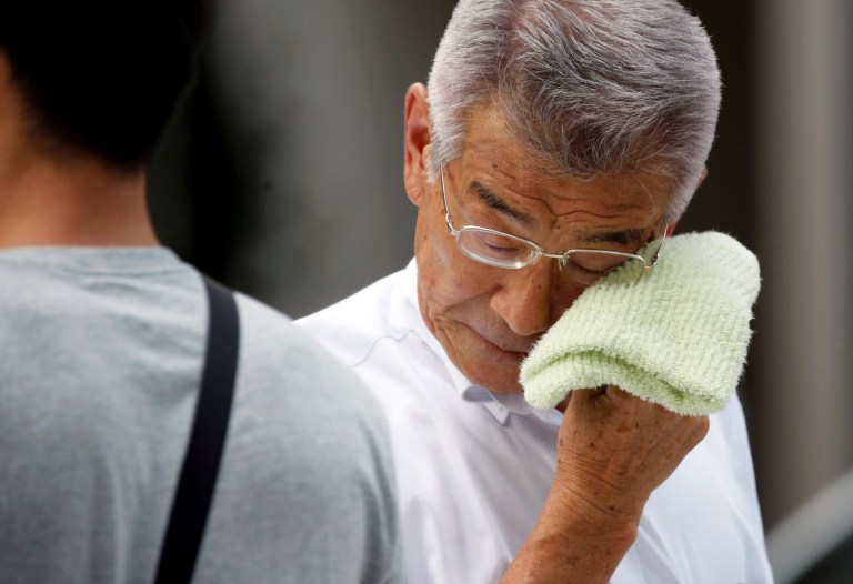 A businessman wipes his face while walking on a street during a heatwave in Tokyo, Japan July 23, 2018. REUTERS/Issei Kato