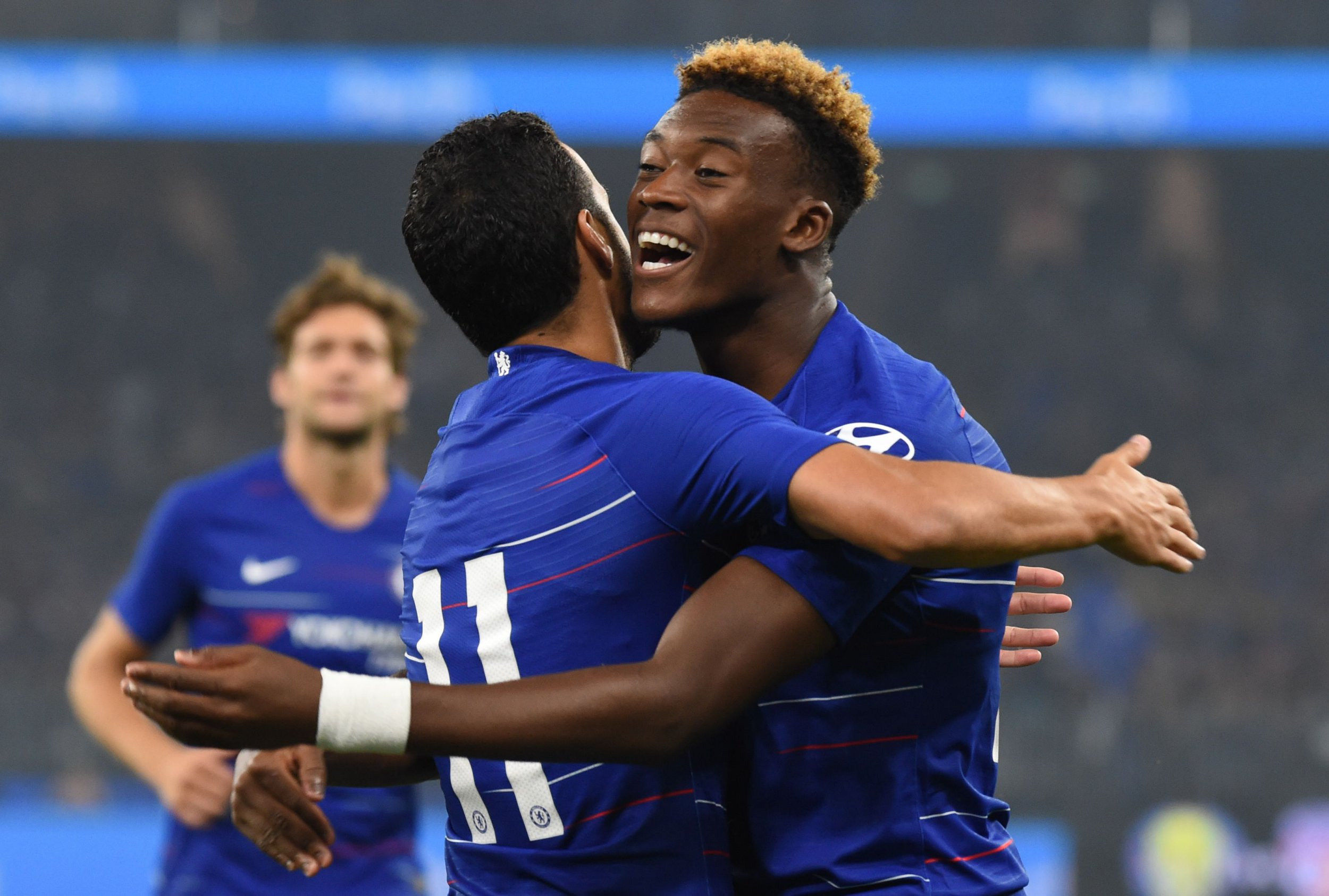 Chelsea's Callum Hudson-Odoi (R) celebrates with teammate Pedro after his cross helped in scoring his team's first goal against Perth Glory during their friendly football match at Optus stadium in Perth on July 23, 2018. / AFP PHOTO / Greg Wood / -- IMAGE RESTRICTED TO EDITORIAL USE - STRICTLY NO COMMERCIAL USE --GREG WOOD/AFP/Getty Images