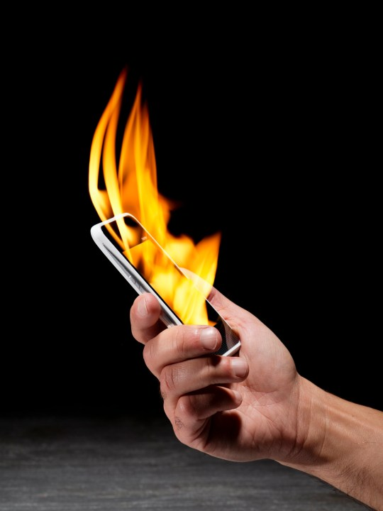 Man's hand holding a smartphone that is on fire