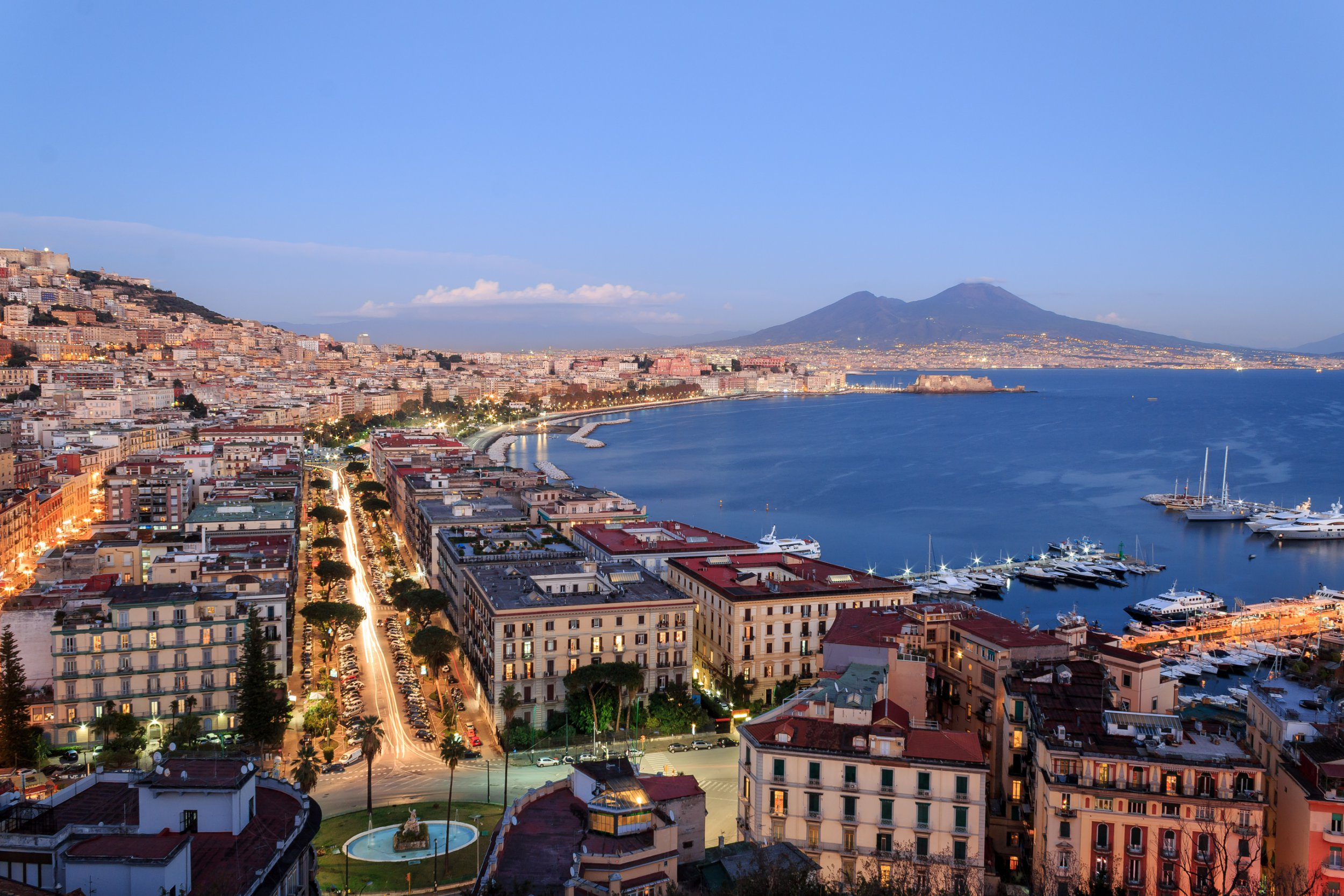 Italy, the bay of Naples in the evening, with Mount Vesuvius Volcano in background and city lights on.