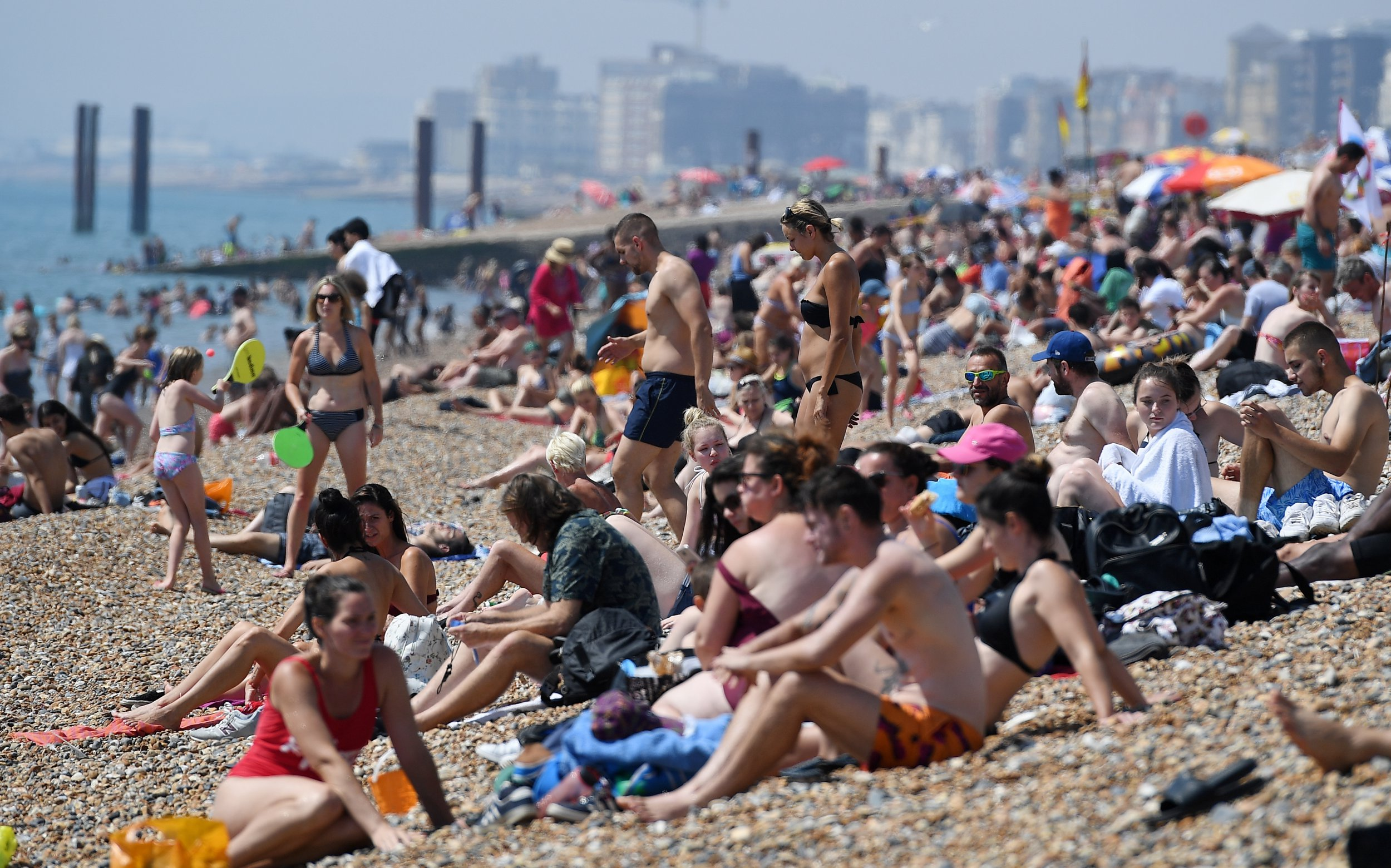 epa06911839 People enjoy the warm weather on Brighton beach in Brighton, Britain, 26 July 2018. Britain is set for its hottest day of the year with temperatures expected to reach close to 36-degree Celsius as the heatwave continues across the country. EPA/ANDY RAIN