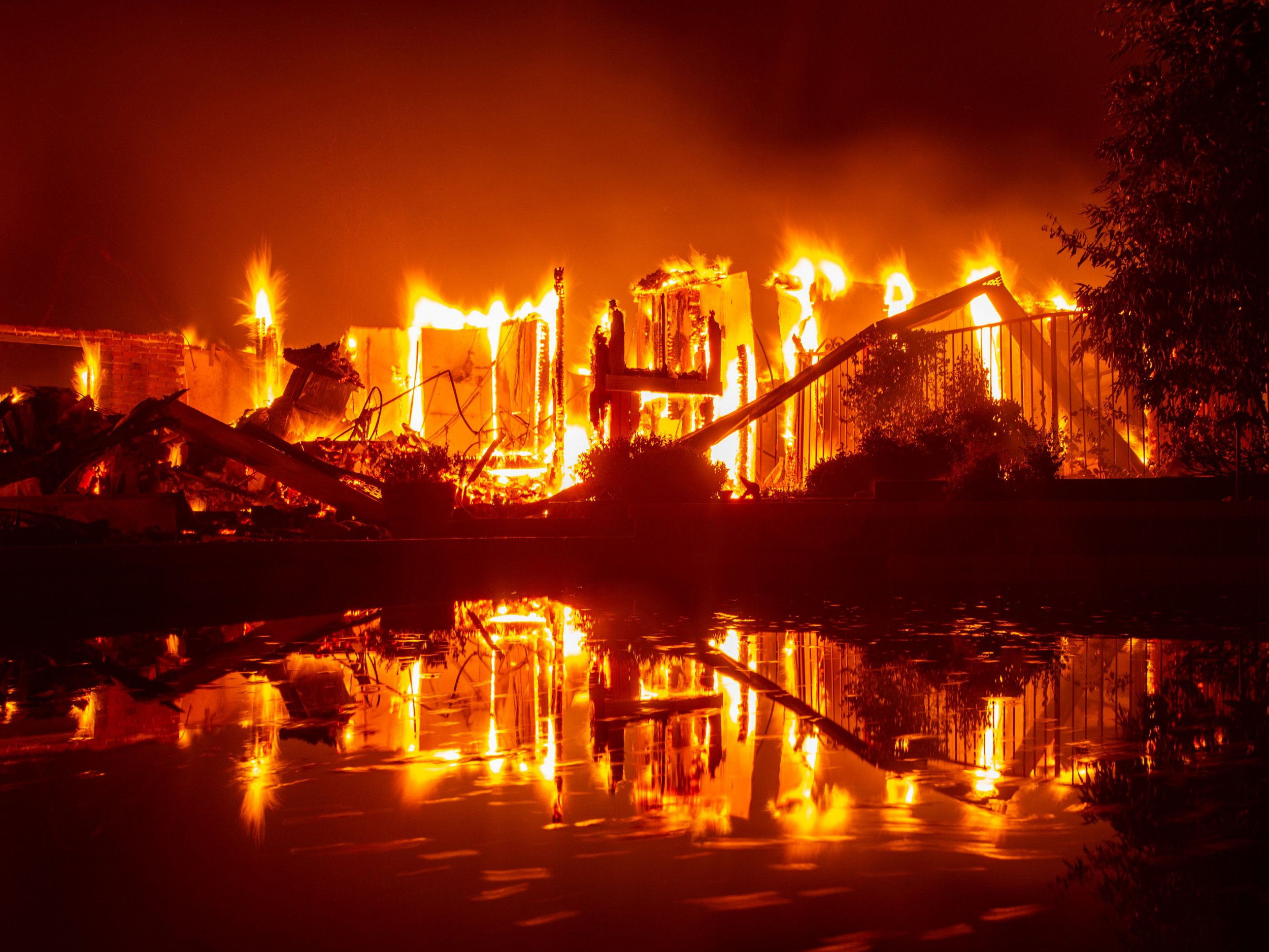 A burning home is reflected in a pool during the Carr fire in Redding, California on July 27, 2018. One firefighter has died and at least two others have been injured as wind-whipped flames tore through the region. / AFP PHOTO / JOSH EDELSONJOSH EDELSON/AFP/Getty Images