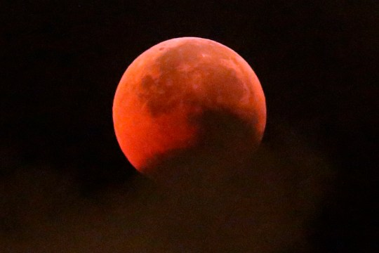 A blood moon rises during a complete lunar eclipse, in Hong Kong, Saturday, July 28, 2018. Curiosity and awe have greeted a complete lunar eclipse, the longest one of this century and visible in much of the world. (AP Photo/Kin Cheung)