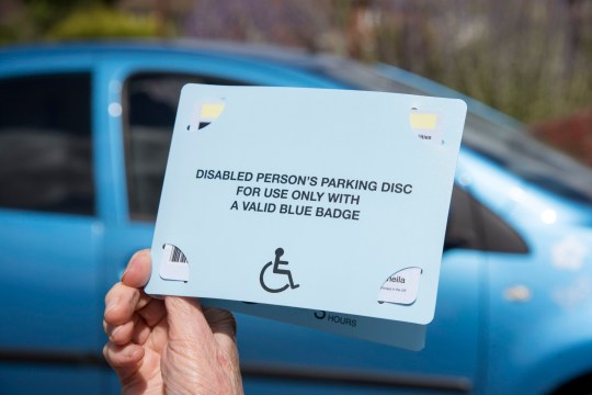 Woman's hands holding a Blue Badge parking disc issued in the UK to disabled drivers. (Photo by: Education Images/UIG via Getty Images)