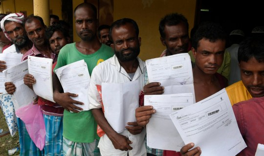 epa06918908 Villagers wait outside a National Register of Citizens (NRC) verification centre as security personnel keep up vigil in Morigaon district of Assam, India, 30 July 2018. The final draft of NRC was released in Guwahati on 30 July 2018 where Millions of applicants have been left out of the draft National Register of Citizens (NRC) in Assam. The NRC updation process is continuing in Assam under the supervision of Supreme Court to identify the illegal foreigners residing in the state. EPA/STR