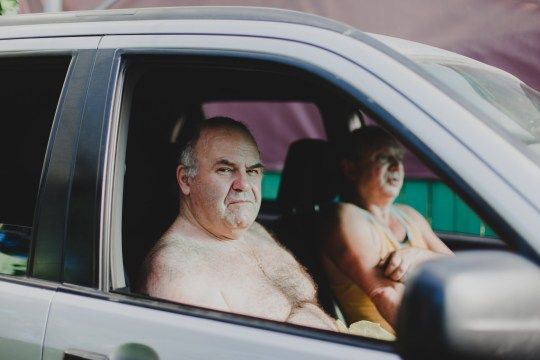 Two men sitting in a car. One of them is looking into the camera, the other is scratching his right hand.