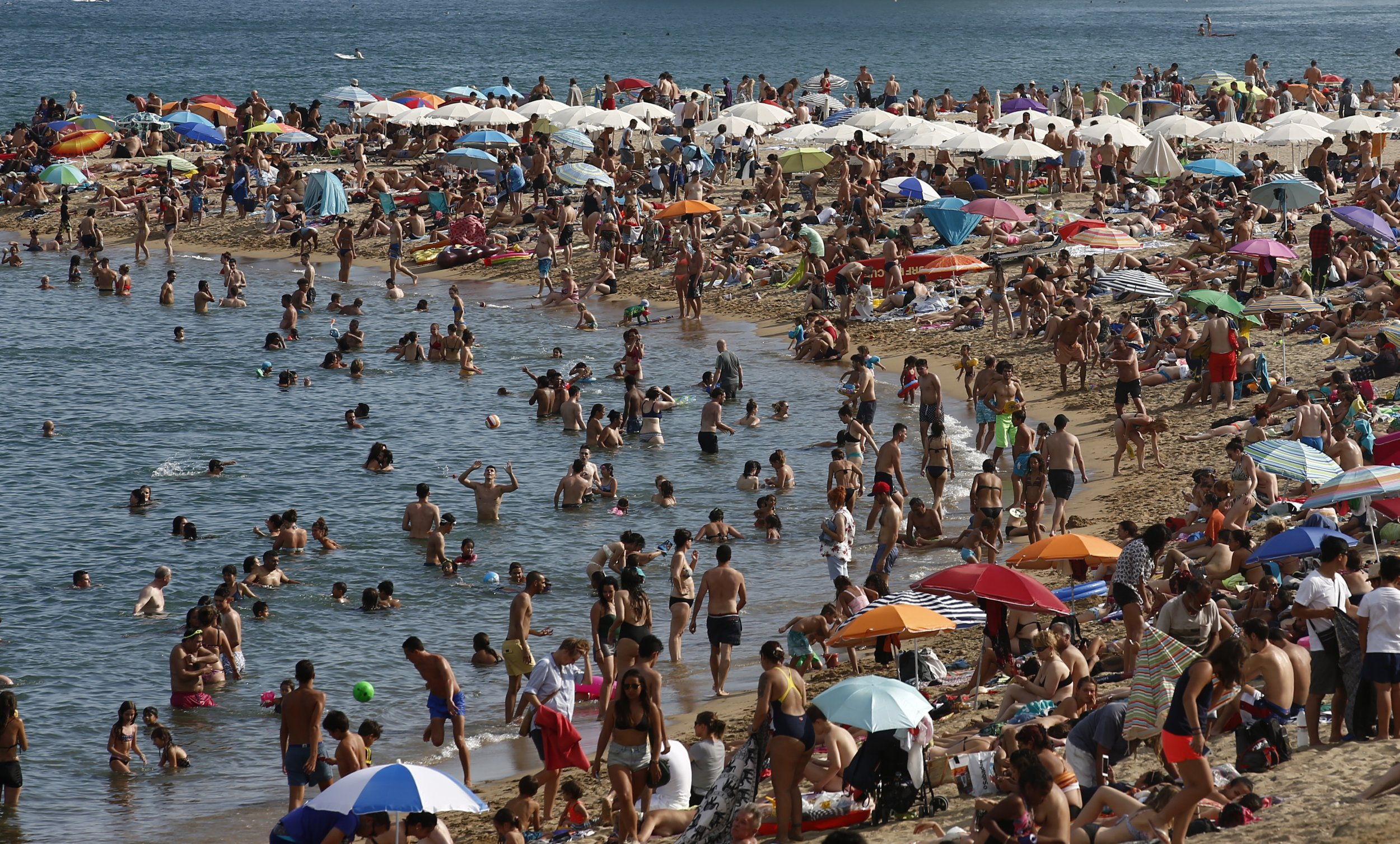 People sunbathe on a beach in Barcelona, Spain, Wednesday, Aug. 1, 2018. Much of Spain is on alert as the country's weather agency warns that temperatures could surpass 40 degrees Celsius (104 Fahrenheit) due to a hot air mass moving northward from the African continent. (AP Photo/Manu Fernandez)