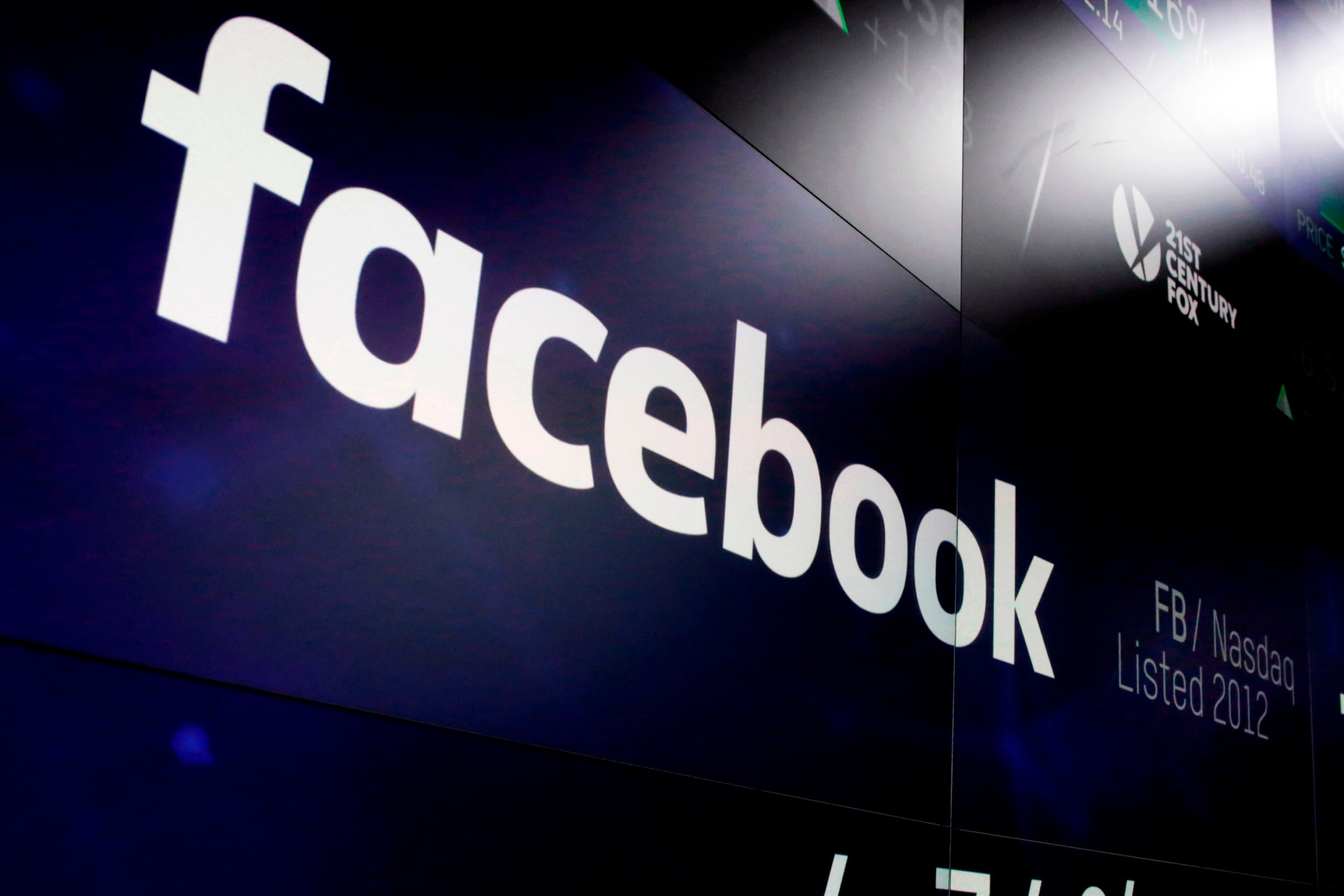 FILE - In this March 29, 2018, file photo, the logo for Facebook appears on screens at the Nasdaq MarketSite in New York's Times Square. Facebook is spending heavily to avoid a repeat of the Russian interference that played out on its service in 2016. Its adversaries are wily, more adept at camouflaging themselves and apparently aren???t always detectable by Facebook???s much-vaunted artificial intelligence systems. (AP Photo/Richard Drew, File)