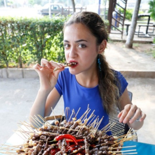 """Pic shows: Turkish Ceren Yilmaz from Antalya managed to eat 255 sish kebab in only 23 minutes during a restaurant's competition in Turkey A young woman who weighs just seven stones has broken local records by scoffing 255 shish kebab skewers in 23 minutes to win an eating competition. The event took place at a restaurant in the coastal town of Antalya, a gateway to Turkey's southern Mediterranean region known as the Turquoise Coast. Ceren Yilmaz left spectators open-mouthed after she downed four kilogrammes (8.8 lbs) of meat as well as salad, a load of bread, three glasses of ayran (a yoghurt-based drink) and two glasses of water. According to reports, the 21-year-old Turkish student, who weighs 45 kilogrammes (7 stone), was initially written off by restaurant owner Ilyas Demir for being too slight. However, Yilmaz stunned everyone by smashing previous records and claiming the top prize of a smartphone worth 5,000 TRY (754 GBP). The 21-year-old also won a gold nugget worth 306 TRY (47 GBP) and free meals at the restaurant for the next four months. Yilmaz said: """"I ate almost four kilogrammes of meat and broke my own record."""" However, the slender youngster also broke the overall women???s record too, previously held by Busra Canimoglu who ate 194 shish kebabs in 18 minutes. In the men???s category, the record is 300 shish kebabs."""