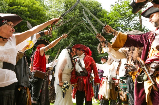 Sarah Kirsty Page, 28, and Wayne Mark Truman, 43, leave their wedding through a gauntlet of swords, in the gardens of Matlock Bath, Derbs. See Ross Parry copy RPYPIRATE: A Captain Jack Sparrow lookalike has tied the knot with his Pirates of the Carribean-mad girlfriend in a wacky PIRATE themed wedding. Wayne Truman, 43, walked down the aisle instead of the plank with his new bride Sarah, 28, following their colourful nuptials on Saturday (4/8). The madcap pair had a day to treasure as they said their vows in front of hundreds of people - all dressed as pirates - at the Matlock Bath Mutiny festival.