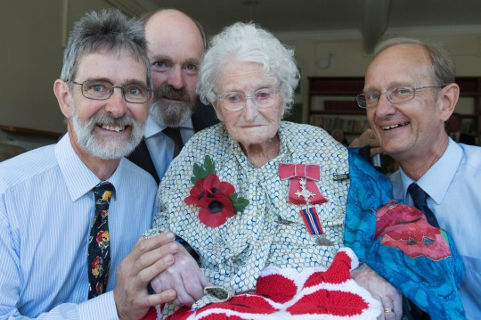 Britain's longest-serving poppy seller, 103-year-old Rosemary Powell, surrounded by her sons (left to right) Anthony, Nicolas and Giles, after she was presented with an MBE at her retirement home in west London by Vice Lord-Lieutenant of Greater London, Colonel Jane Davis. PRESS ASSOCIATION Photo. Picture date: Monday August 6, 2018. The great-grandmother, from London, was included in this year's Queen's Birthday Honours List for voluntary service to the Royal British Legion Poppy Appeal, having spent 97 years collecting for the charity. See PA story ROYAL Investiture. Photo credit should read: Stefan Rousseau/PA Wire