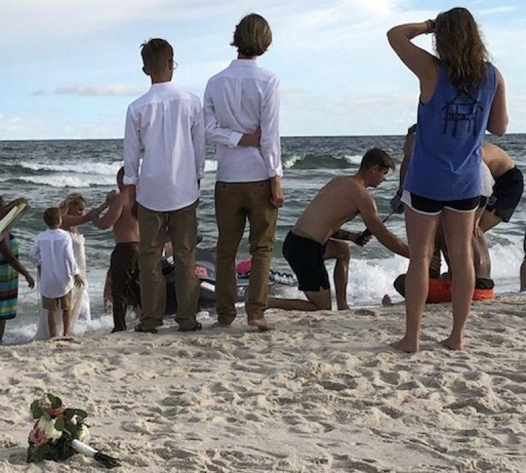 The scene after the rescue. See SWNS story NYDROWN; A groom bravely interrupted his wedding photographs to strip down and dive into the ocean to rescue a drowning teenager. Zac Edwards, 37, was posing for photos with his bride Cindy Edwards, 32, when a woman brought their attention to a teenager struggling in the water on August 2. The newlywed marine science technician, immediately rushed toward the water in Orange Beach, Alabama, to help the 18-year-old who had been pulled more than 150 feet from the shore on a boogie board. Zac, who works with the US Coast Guard, reached the teenager and propped him up on the boogie board to keeping his head above water. The pair made their way towards the shore against the current but bride Cindy, a sales manager, was worried than her new husband was growing tired. Minutes after diving into the water, brave Zac was assisted by first responders from the Orange Beach Fire and Rescue Department, who had been attending to another emergency on the beach.