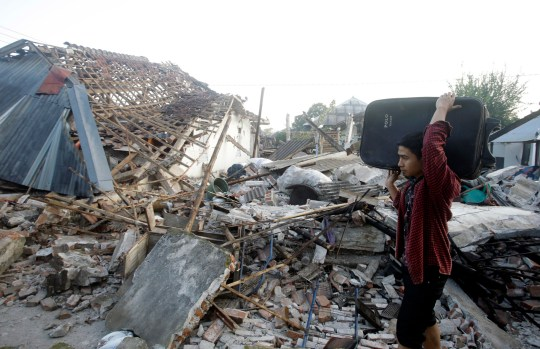 A man carries his belongings past the ruin of houses at a village affected by an earthquake in North Lombok, Indonesia, Thursday, Aug. 9, 2018. The north of Lombok was devastated by the powerful quake that struck Sunday night, damaging thousands of buildings and killing a large number of people. (AP Photo/Firdia Lisnawati)