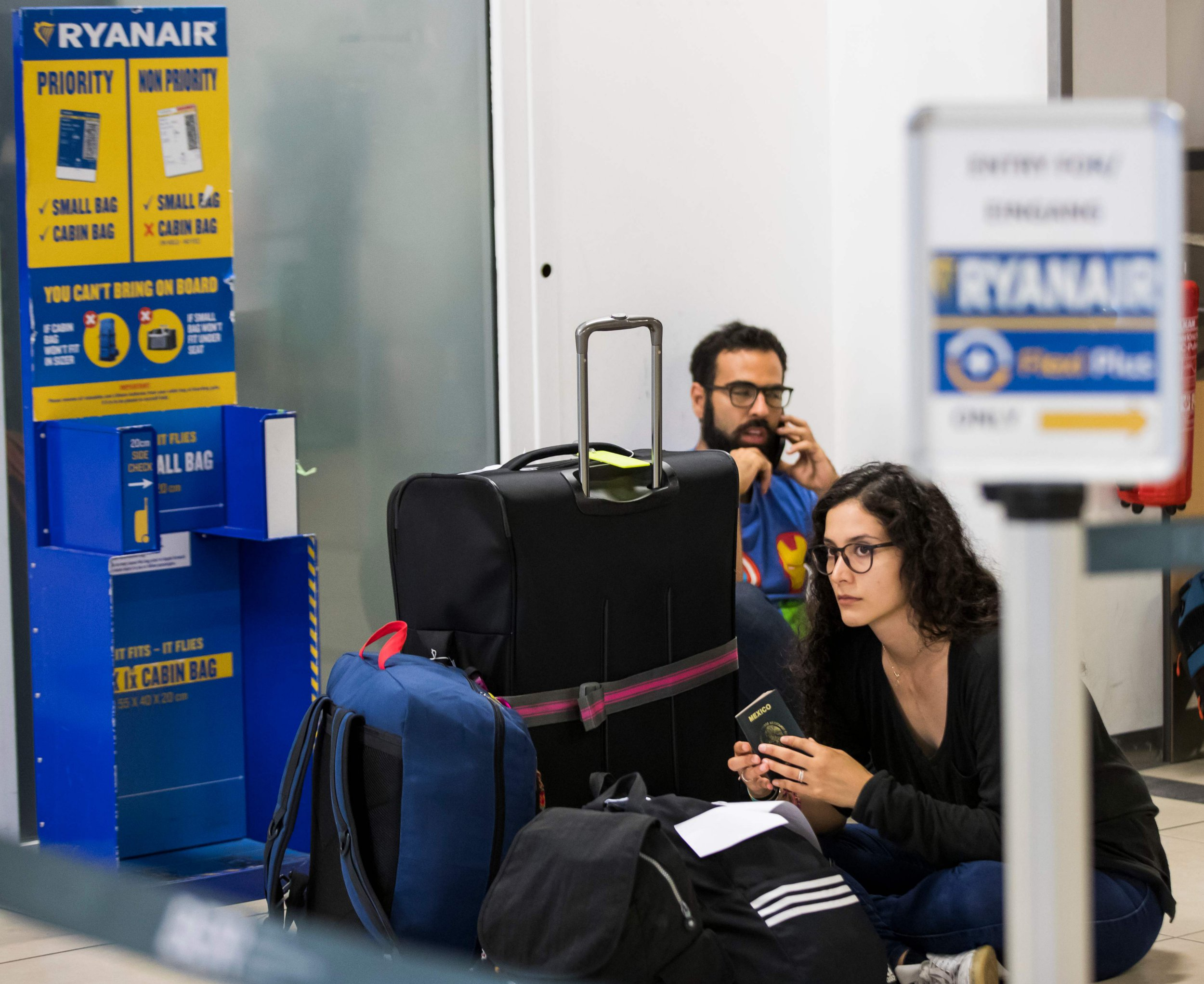 Ryanair passengers Diego Gomez (L) and Maria Vargas (C) from Mexico sit on the terminal floor at Schoenefeld Airport in Berlin on August 10, 2018, after their Ryanair flight was cancelled because of a pilots strike. - Ryanair pilots are staging a 24-hour walk-out involving staff in Germany, Sweden, Ireland, Belgium and the Netherlands. About 50,000 passengers are understood to have been told of cancellations on 400 flights, 250 of those in Germany due to the strike action. (Photo by Odd ANDERSEN / AFP)ODD ANDERSEN/AFP/Getty Images
