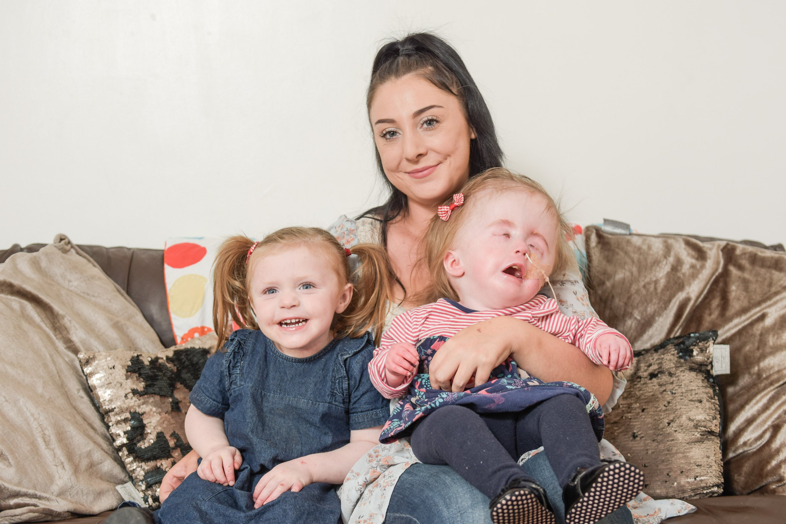 MERCURY PRESS. 10/08/18. Pictured: Pearl Jones, 24 with her daughters Annabella (left) and Aubrey (right). A baby girl has had to have her eyes stitched shut as her eyelids were stretched by her oversized head which swelled to the size of a four year olds due to a rare condition. Aubrey Jones, 19 months, suffers from the rare condition hydrocephalus, which has caused her head to grow much larger than her three-year-old sister Annabella Joness. The tots condition is so severe that her mum Pearl Jones, 24, claims she was offered a late termination as she was told it was unlikely Aubrey would survive for more than three hours. But Aubrey beat all the odds and came through six surgeries to be allowed home with her loving mum and sister, where she now lives a comfortable' life. SEE MERCURY COPY