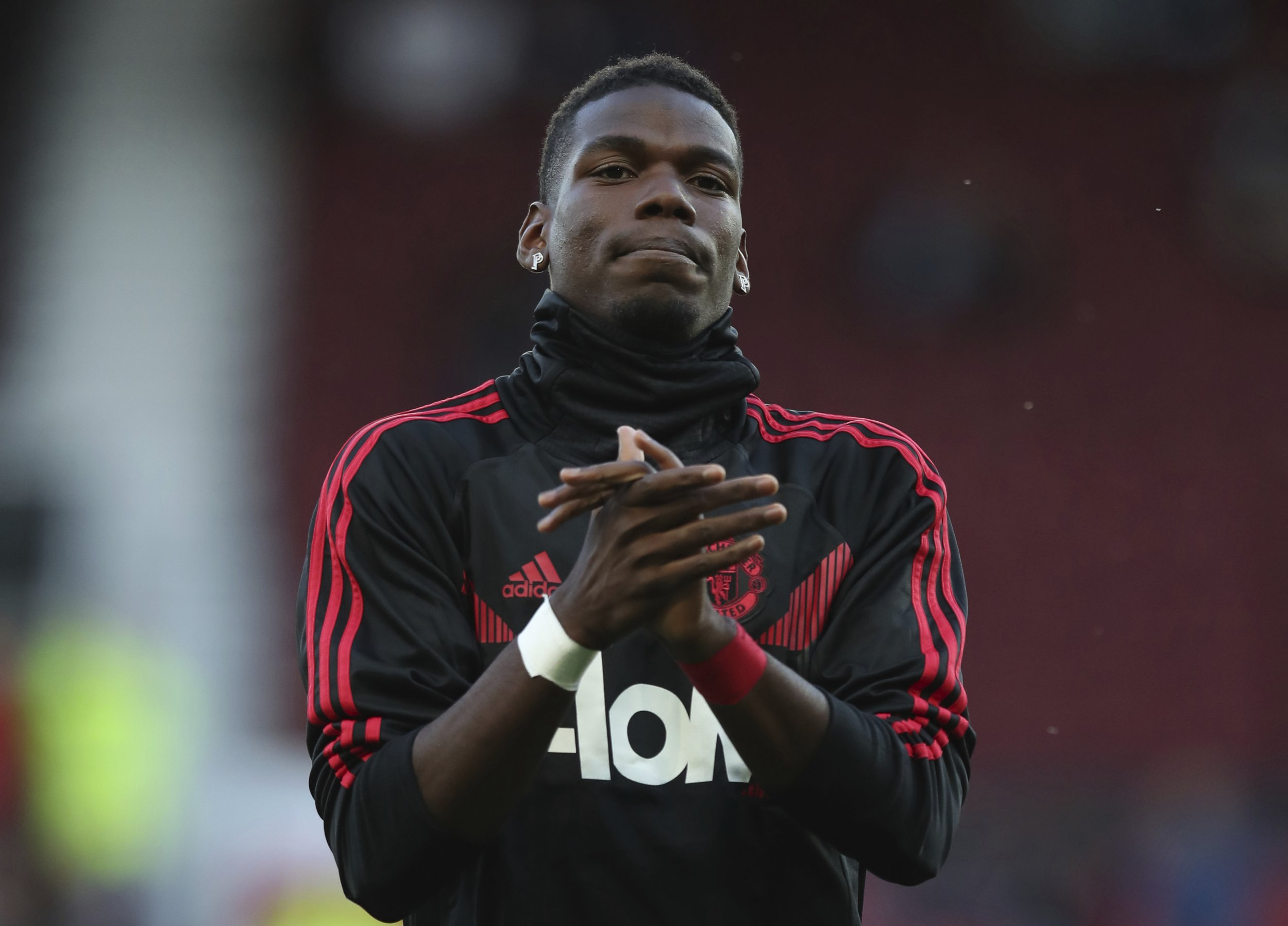 Manchester United's Paul Pogba applauds the fans as he takes part in the warm up prior to the start of the English Premier League soccer match between Manchester United and Leicester City at Old Trafford, in Manchester, England, Friday, Aug. 10, 2018. (AP Photo/Jon Super)